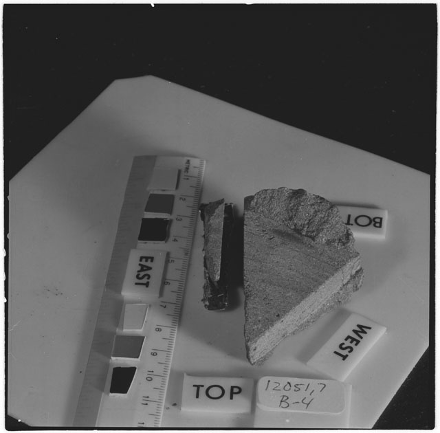 Black and white photograph of Apollo 12 Sample(S) 12051,4,25,26; Processing photograph displaying a post cut sample with an orientation of .