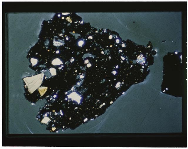 Color photograph of Apollo 12 sample 12033,82; Thin Section photograph displaying grain mount using cross nichols light.