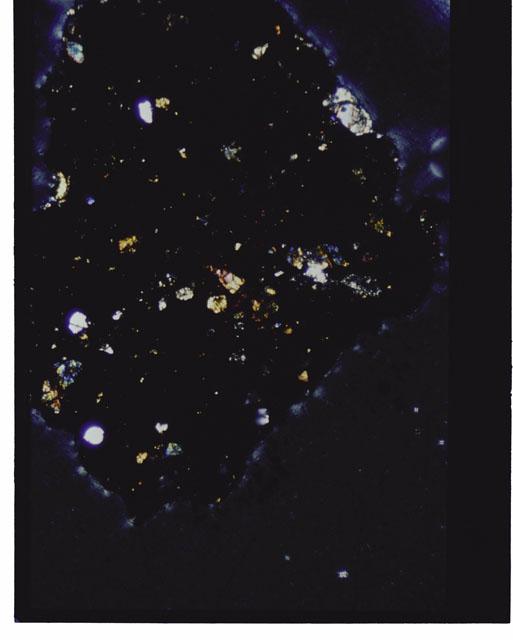 Color photograph of Apollo 12 sample 12070,162; Thin Section photograph displaying grain mount using cross nichols light.