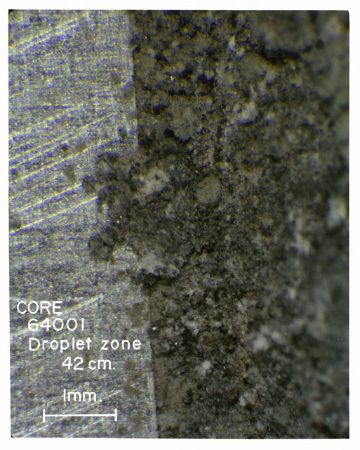 Color photograph of Apollo 16 Core Sample(s) 64001; Processing photograph displaying Core with droplet zone.