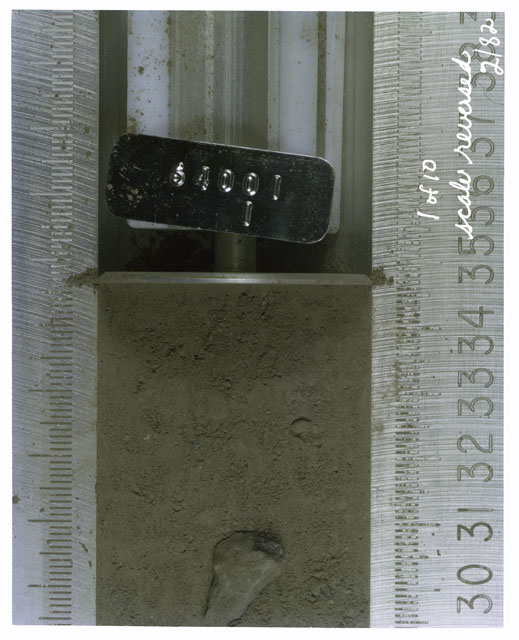 Color photograph of Apollo 16 Core Sample(s) 64001,1; 1 of 10 Processing photograph of displaying Core with scale reversed.