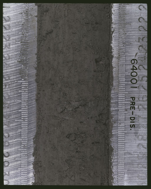 Color photograph of Apollo 16 Sample(s) 64001; 3 of 11 Processing photograph displaying pre-dissection Core at 21.5-30 cm depth.