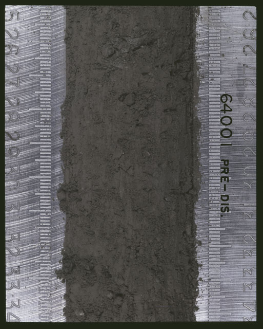 Color photograph of Apollo 16 Sample(s) 64001; 4 of 11 Processing photograph displaying pre-dissection Core at 25-34 cm depth.