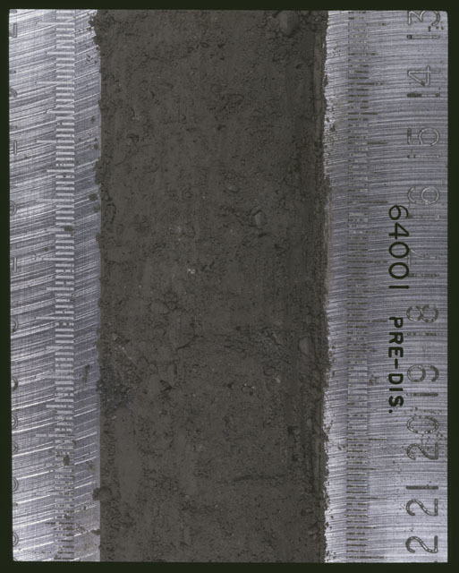 Color photograph of Apollo 16 Sample(s) 64001; 6 of 11 Processing photograph displaying pre-dissection Core at 13-22 cm depth.