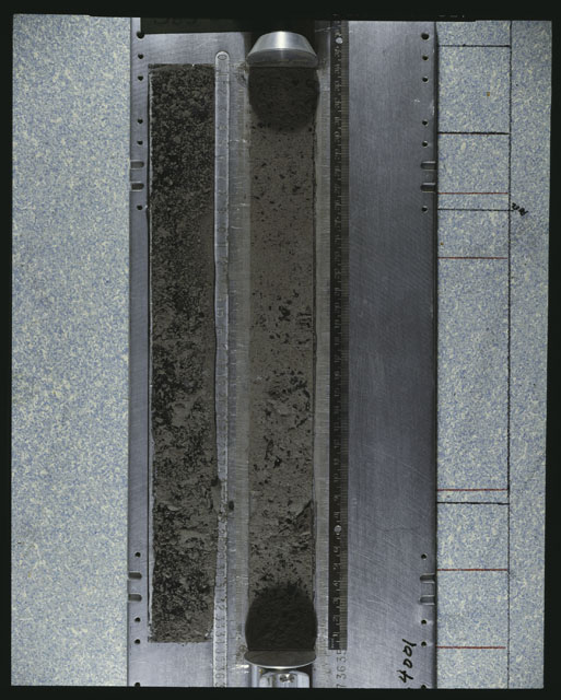 Color photograph of Apollo 16 Core Sample 64001; Processing photograph displaying an overview of the Core core with peel.